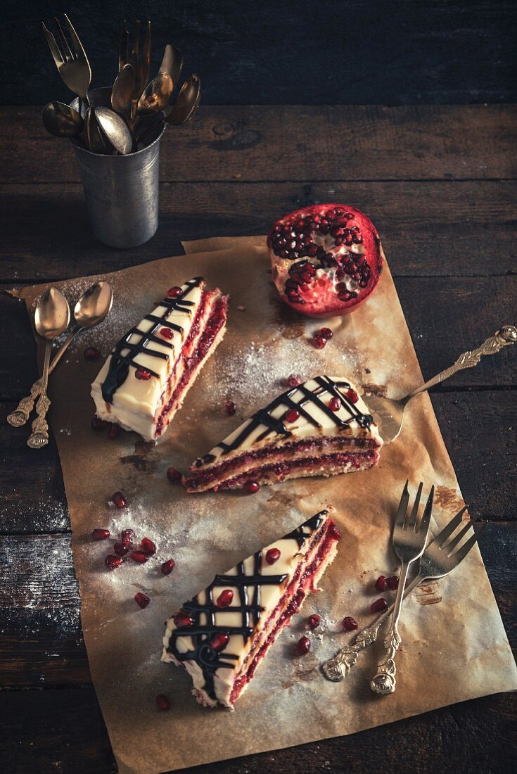 Three slices of white chocolate and pomegranate torte