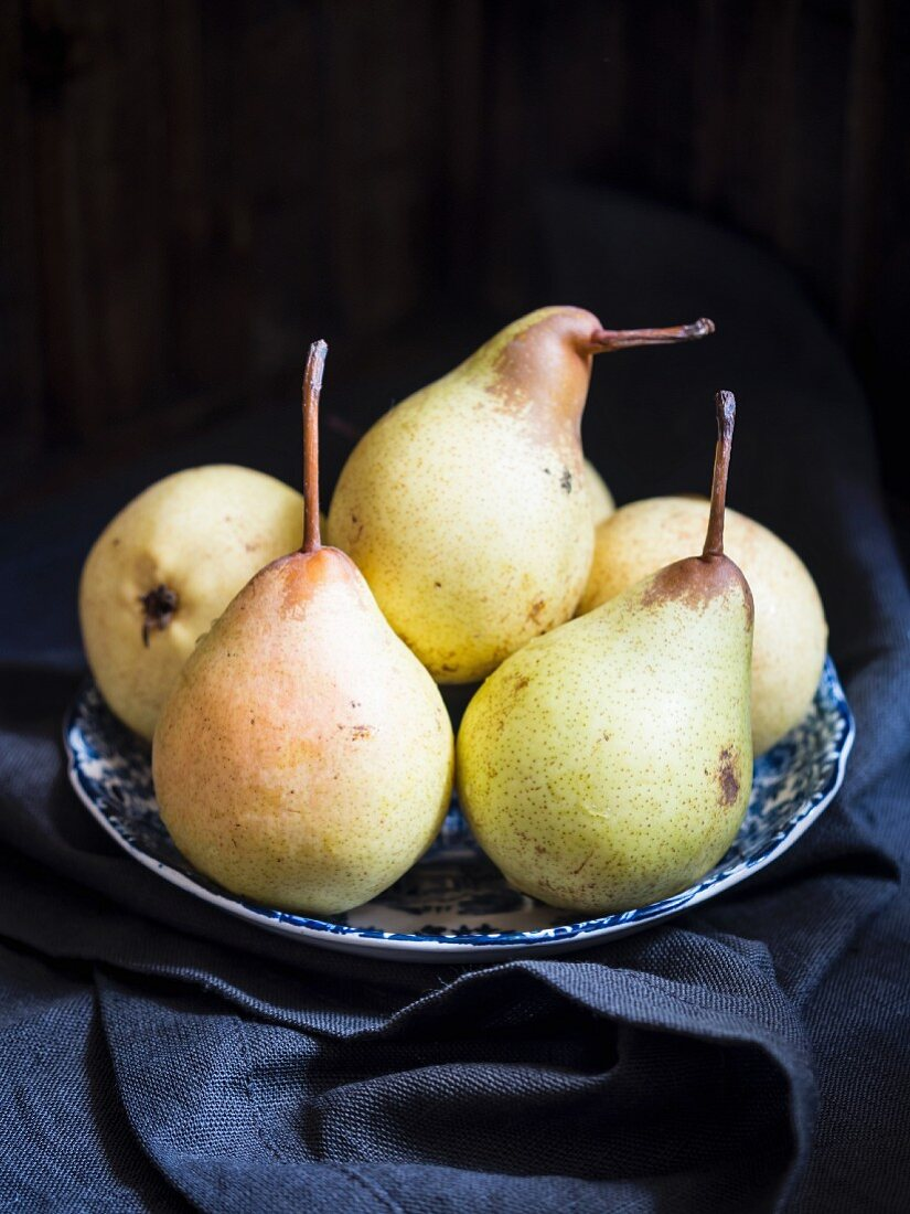 A plate of fresh pears on a dark moody background