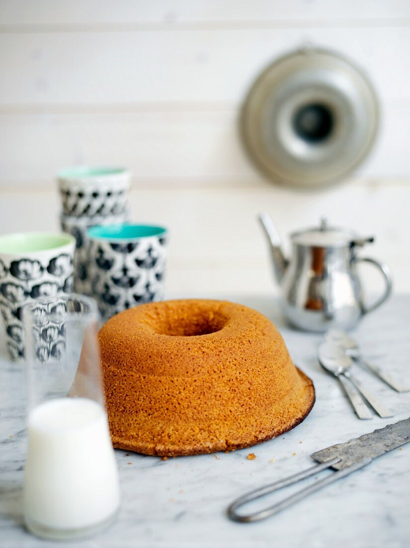 A sponge cake with a jug of milk