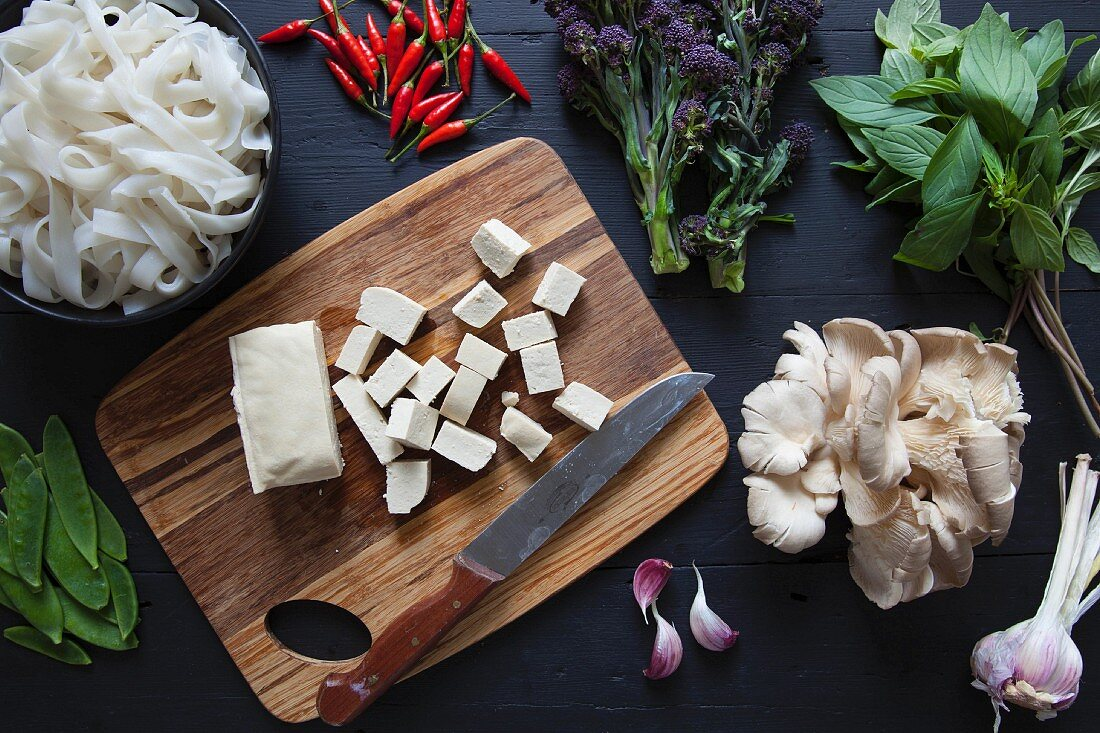 Ingredients for a stir fry: tofu, broccoli, rice noodles, chilli, Thai basil, oyster mushrooms, garlic and snow peas