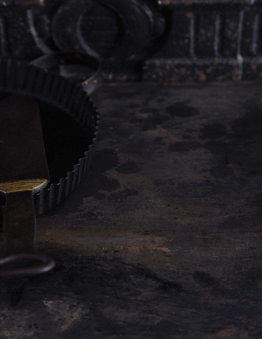 A dark background with various baking utensils
