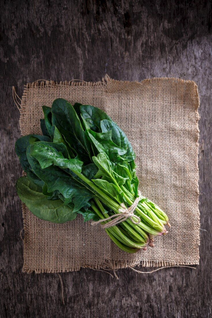 A bunch of spinach on jute (top view)