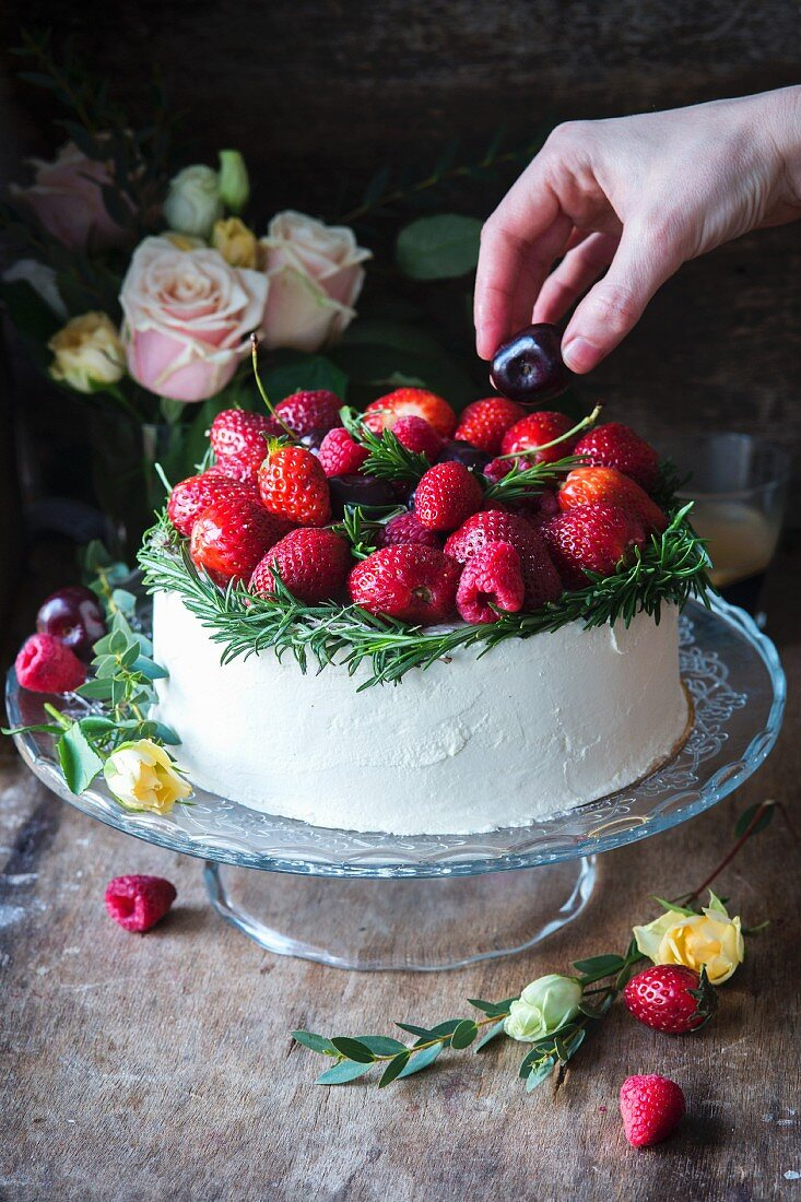 A vanilla buttercream cake garnished with red fruits and rosemary