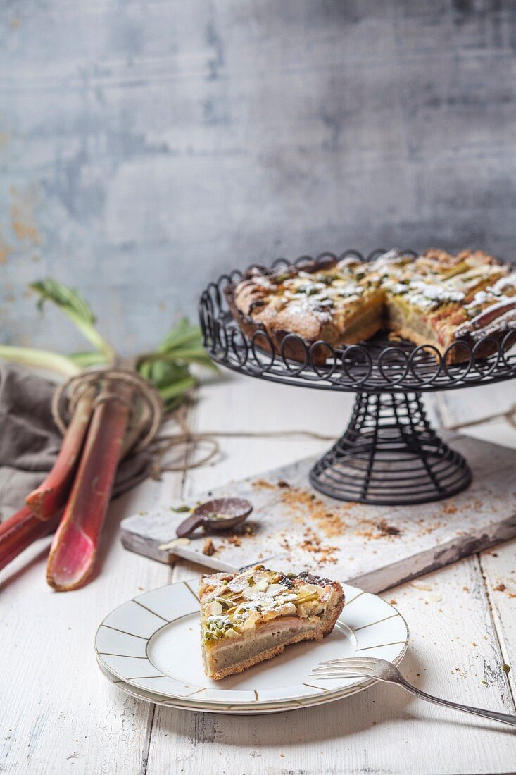 Rhubarb and frangipani tart with pistachios on a plate and a cake stand