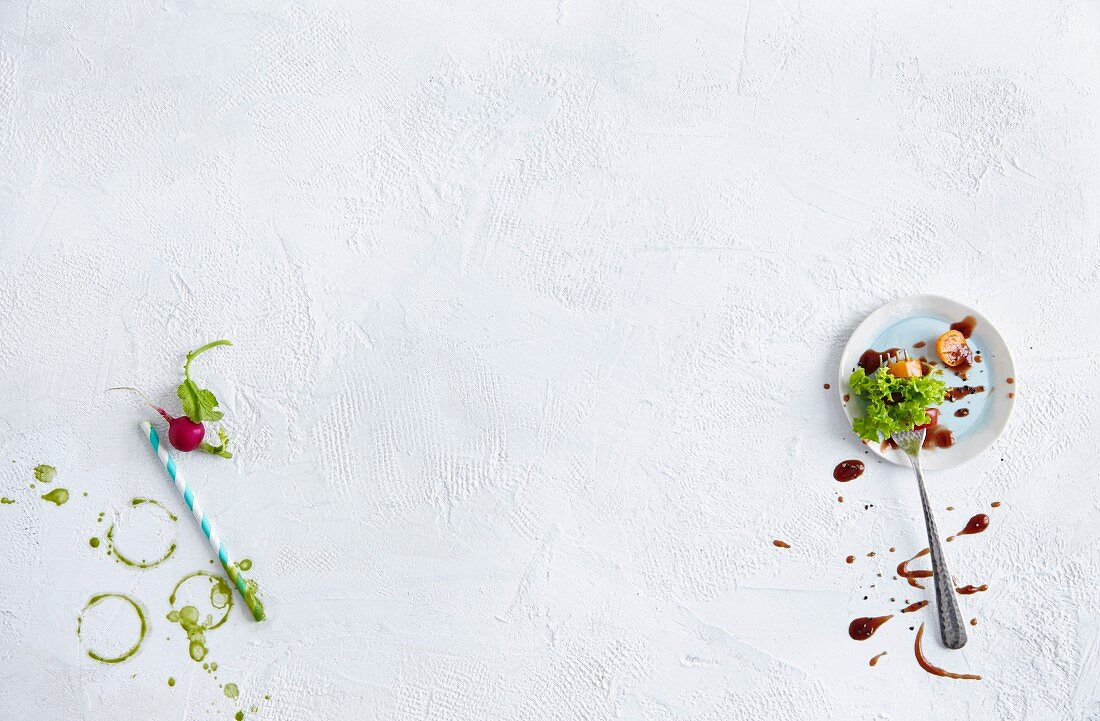 Green smoothie stains, a straw, a radish, and lettuce leaves