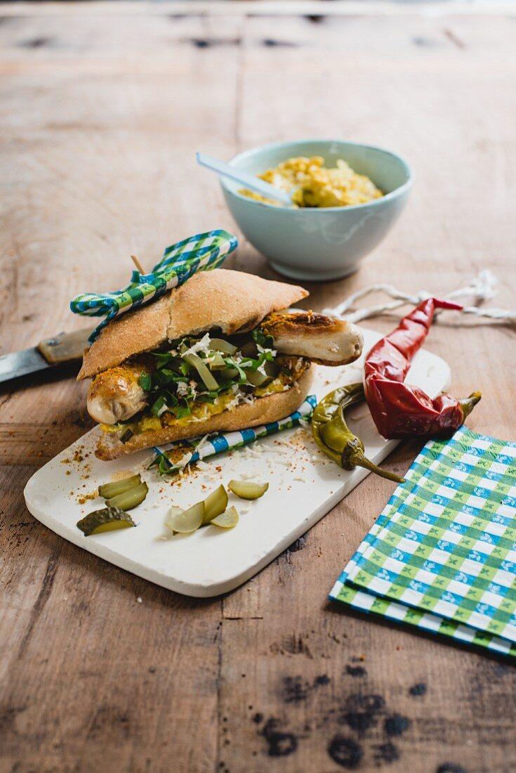 An alpine hotdog with bratwurst, gherkins, chilli and mustard