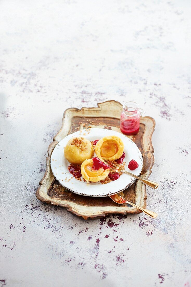 Apricot dumplings with breadcrumbs and raspberry sauce