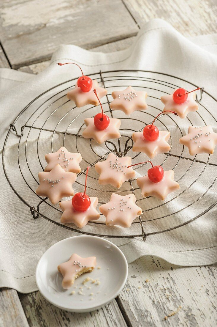 Star biscuits glazed with icing and topped with glace cherries