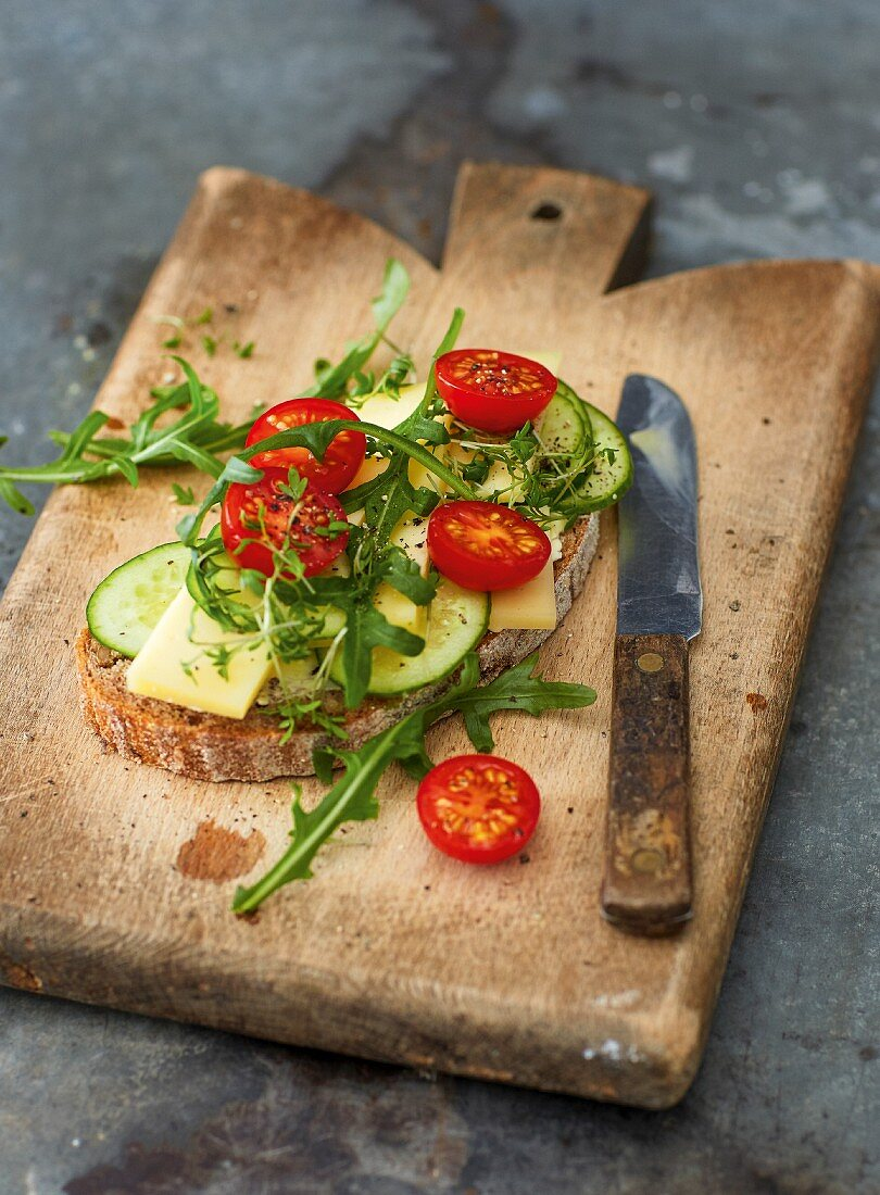 Wholemeal bread topped with cheese, cucumber, rocket and tomatoes