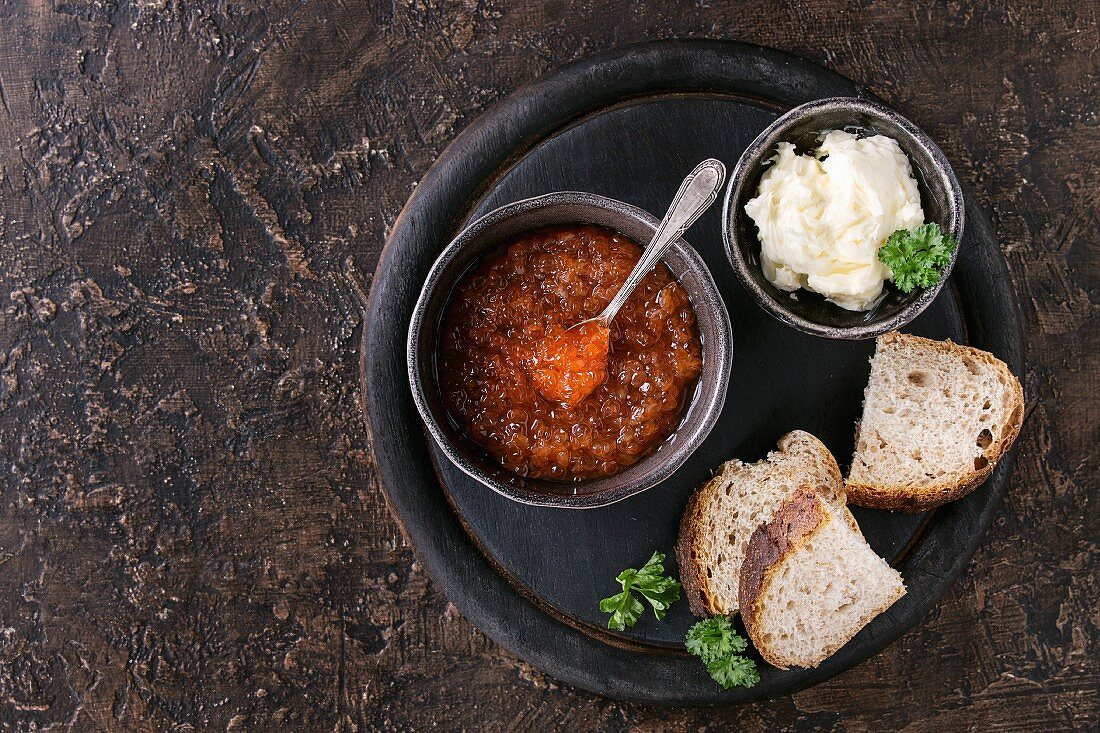 Bowl of red caviar with spoon served with sliced bread, butter and herbs on black wooden chopping board