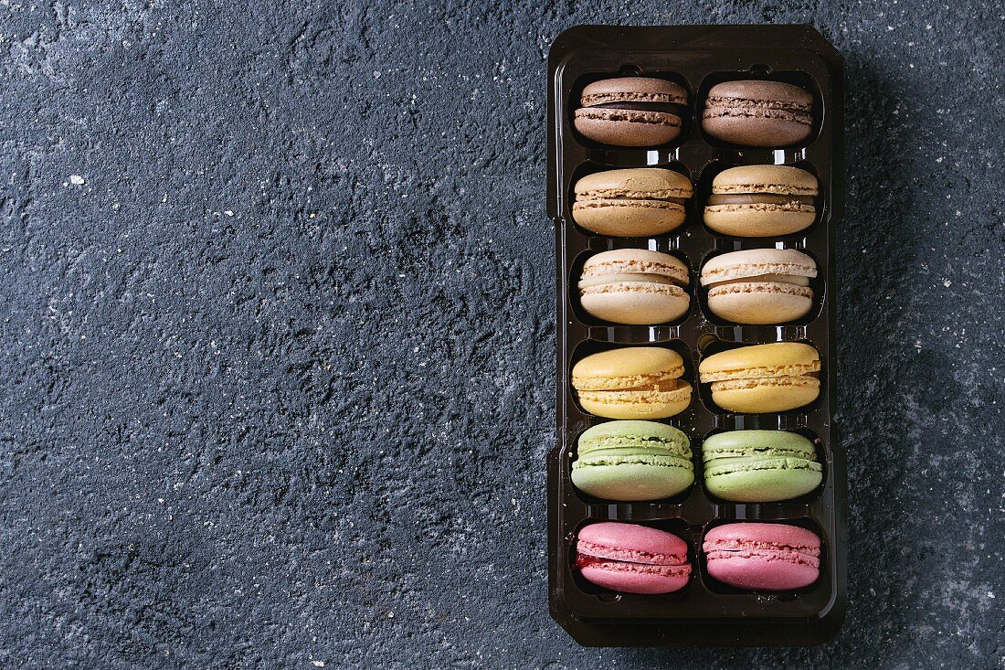 Variety of colorful french sweet dessert macaron with different fillings in balck plastic box