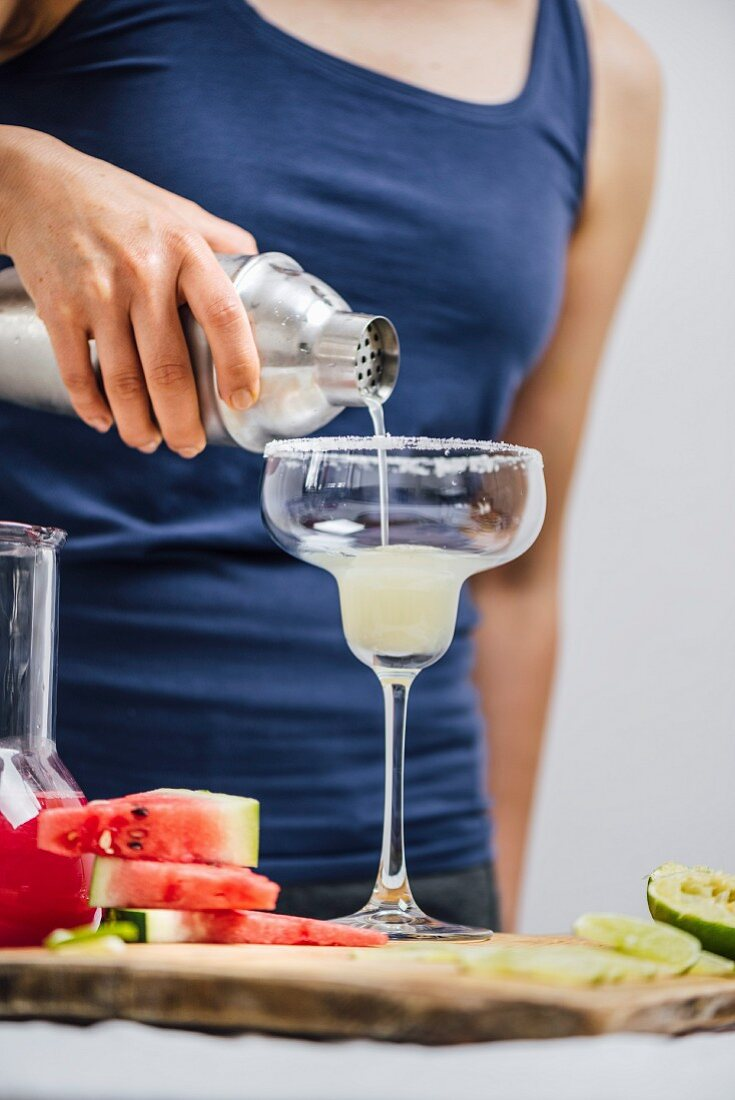A woman pouring margarita from a shaker into a rimmed margarita glass