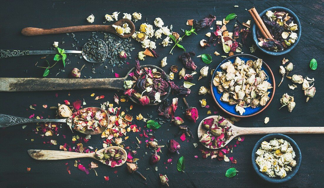 Wooden spoons with dry herbs, flower buds and tea leaves over black scorched wooden background
