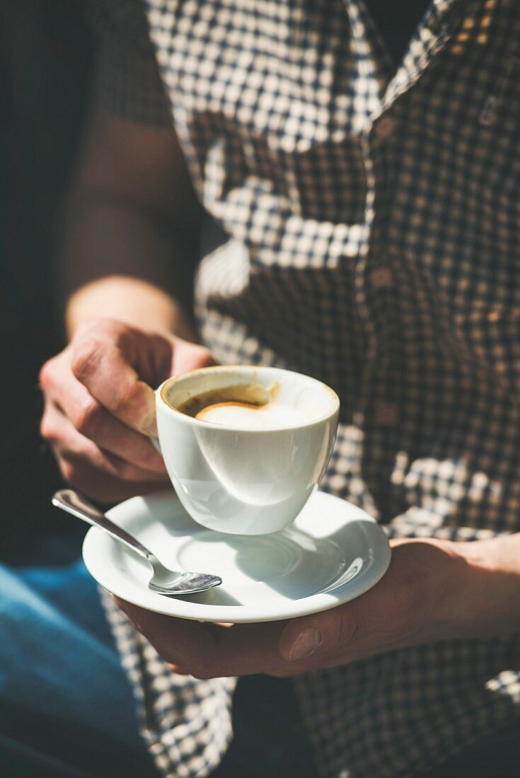 Cup of coffee cappuccino in man s hands in street cafe under sunlight