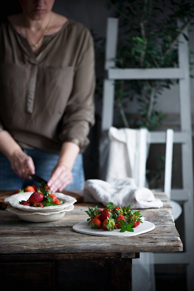 A woman chopping strawberries on a table in a rustic country house kitchen
