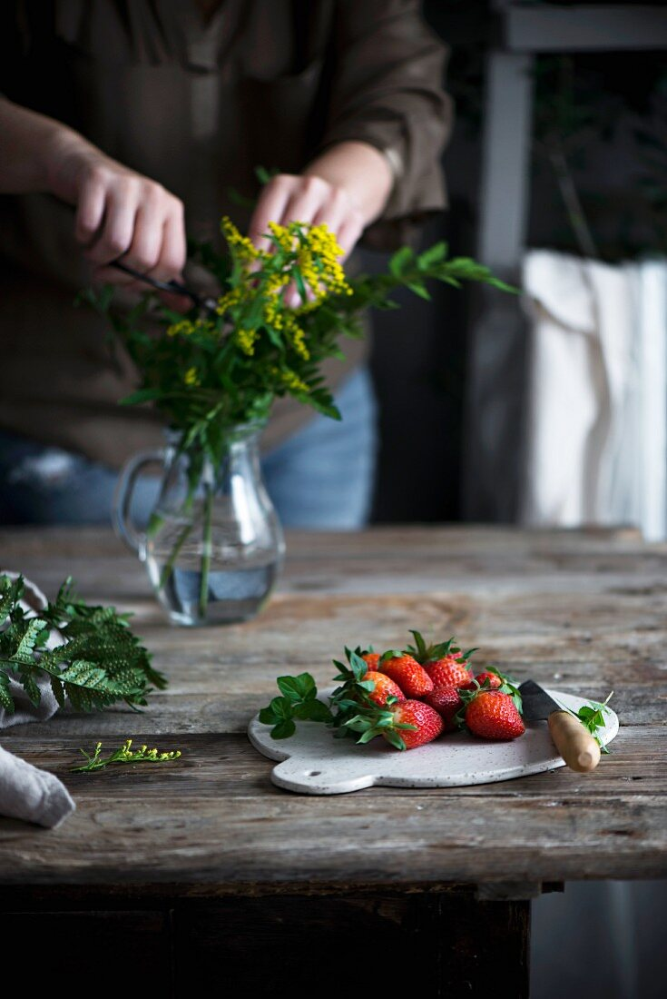 Fresh strawberries on a chopping board and wooden table in a country house kitchen
