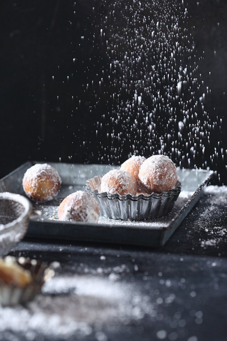 Dusting icing sugar over Castagnole (fried pastries, Italy)
