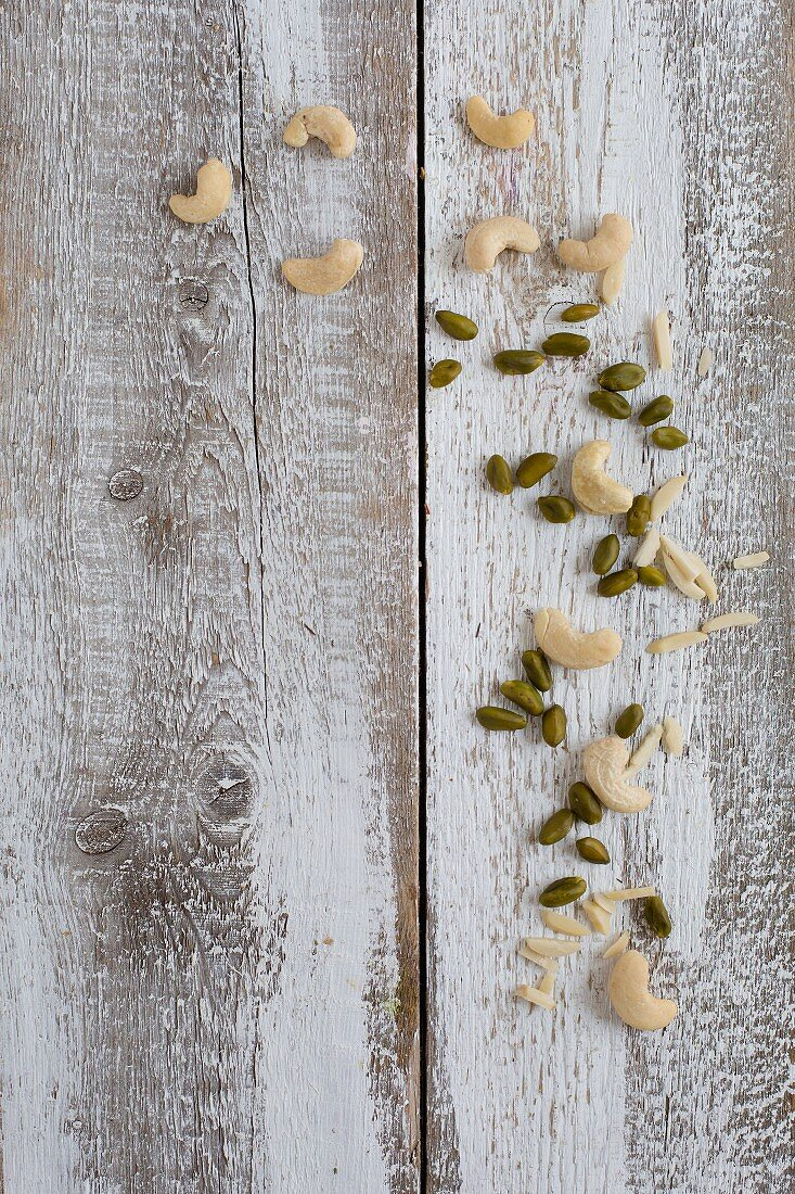 Almond slivers, cashews and pistachios on a wooden background (seen from above)
