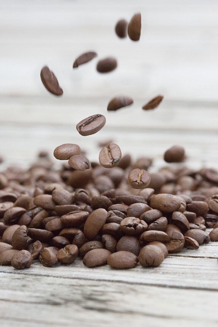 A pile of coffee beans on a weathered gray wood surface and beans falling on the pile from above
