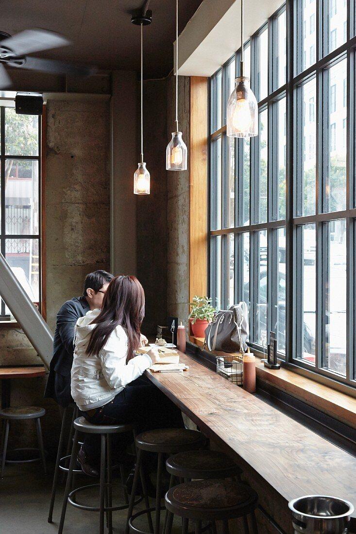 Paar isst gegrillte Käsesandwiches in einem Restaurant (San Francisco, USA)