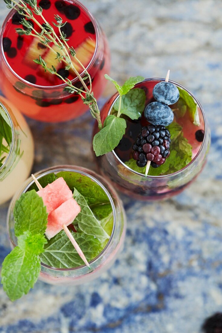 Various cocktails with fruits and herbs (seen from above)