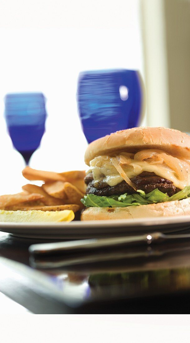 Steak House Burger with Lettuce and a Pickle with French Fries; On a Table with a Glass of Wine