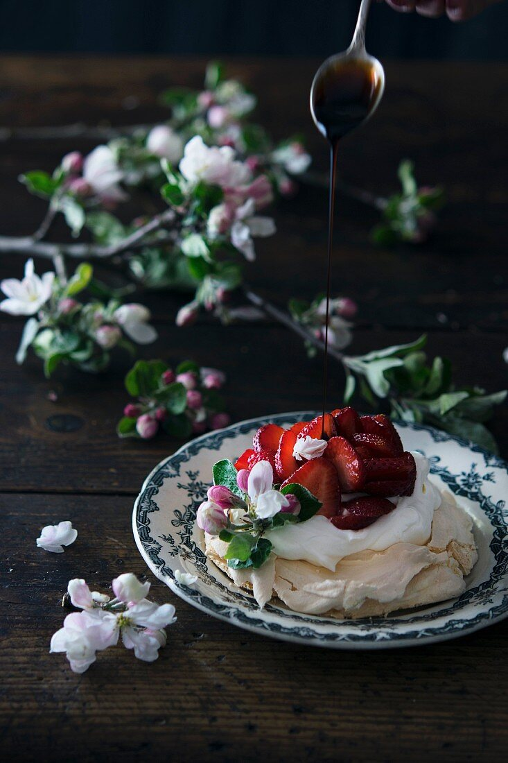 Crema di Balsamico being drizzled onto a strawberry pavlova decorated with fruit blossoms