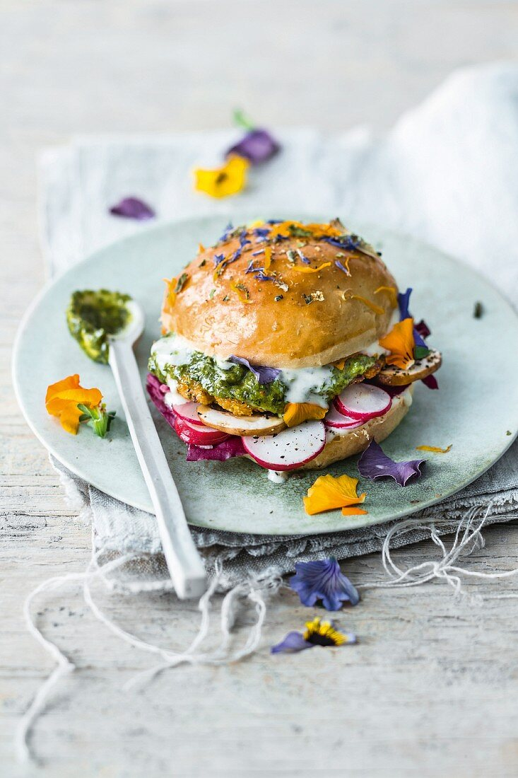 A seitan and millet burger with radishes, mojo verde, and edible flowers