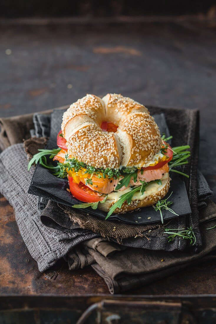 A sesame bagel with salmon, arugula, and cress