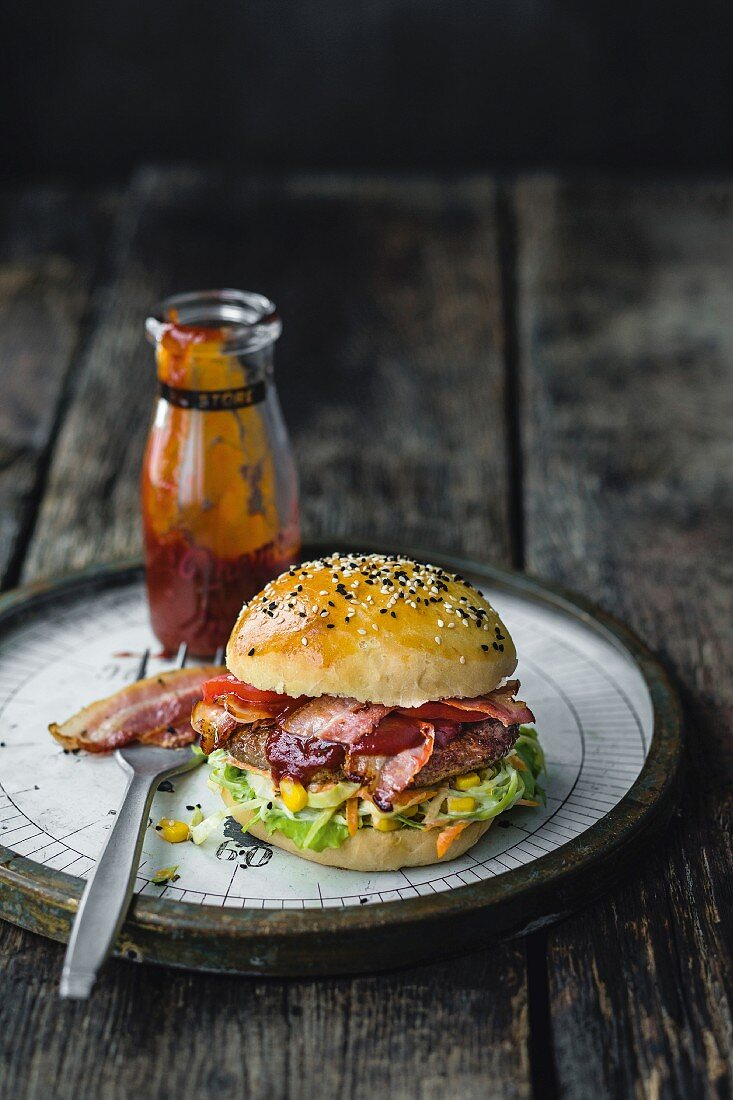 A burger with beef, coleslaw, bacon, tomato and whiskey barbecue sauce
