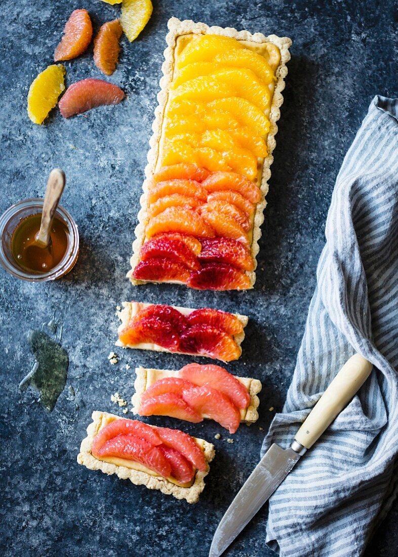 Zitrusfrüchte-Ricotta-Tarte belegt mit Zitrusfrüchten im Farbverlauf