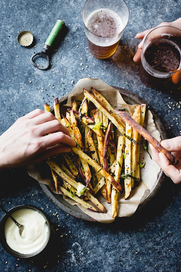 Japanese sweet potato oven fries with wasabi aioli. Hands are holding fries