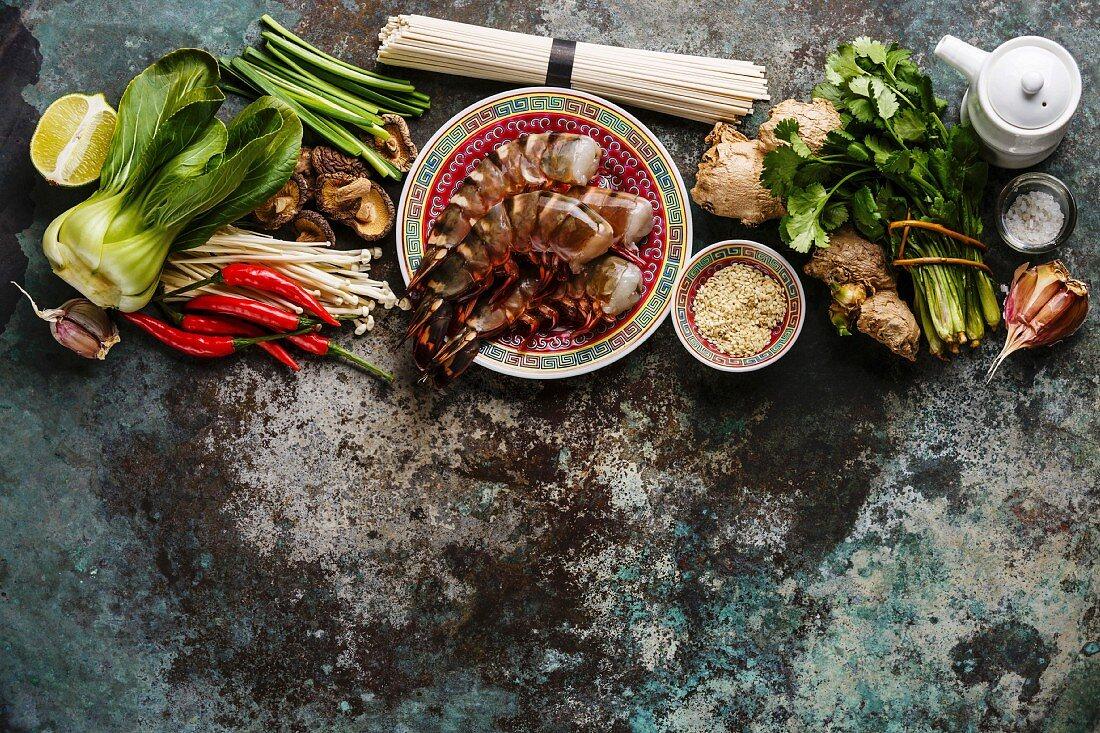 Ingredients for cooking Asian food with Tiger shrimps, udon noodles, mushrooms, greens, vegetables, spices on metal background