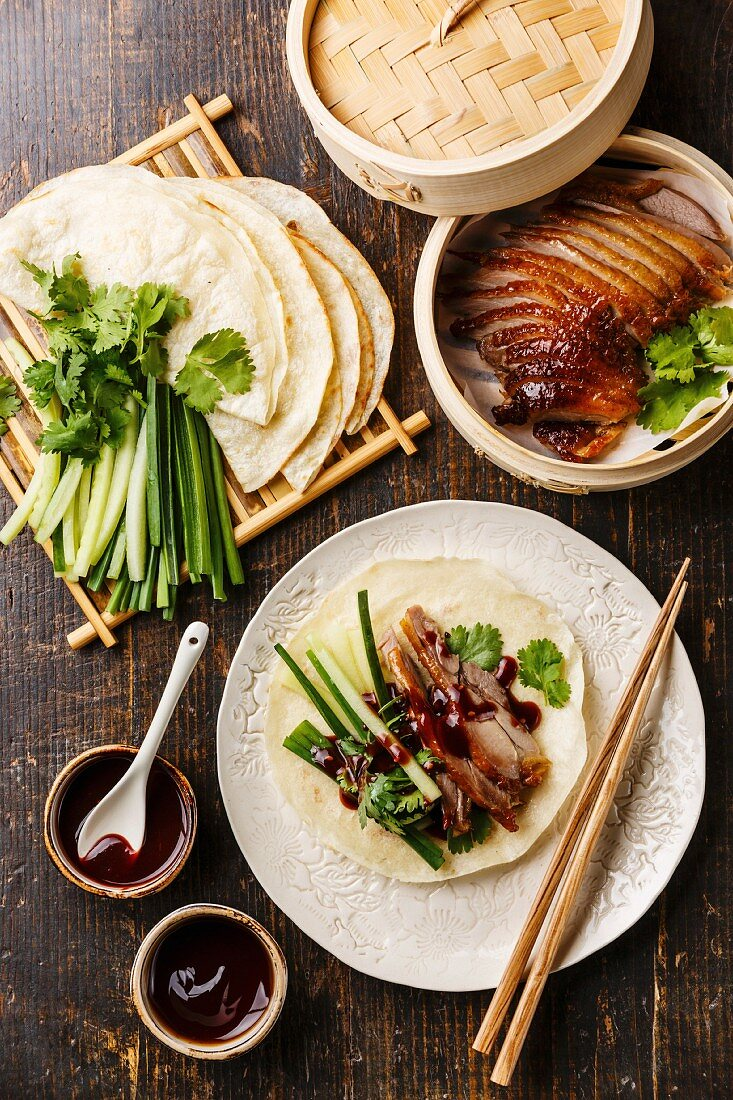 Peking Duck served with fresh cucumber, green onions, cilantro and roasted wheaten chinese pancakes with sauce Hoysin