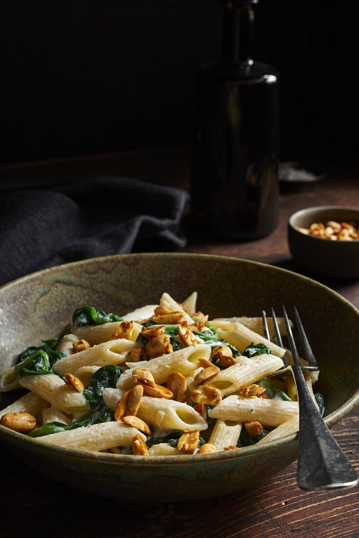 Penne with spinach and caramelised peanuts in goat's cheese sauce