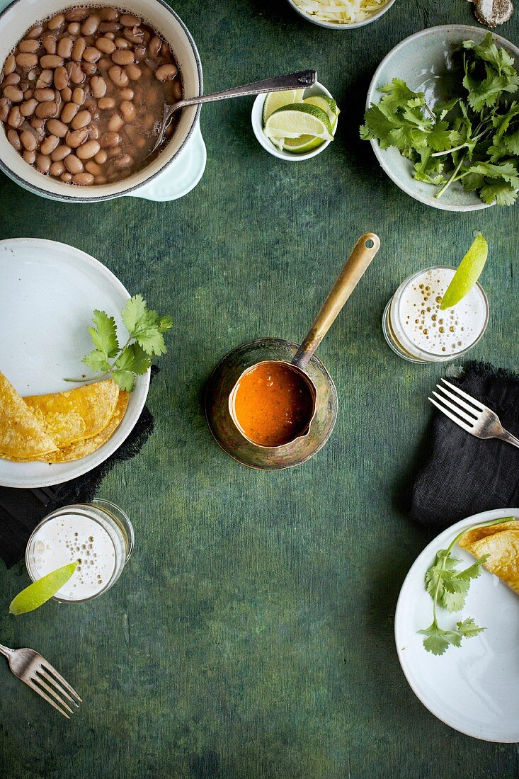 Ranchero Sauce in a vintage copper ladle on a green background