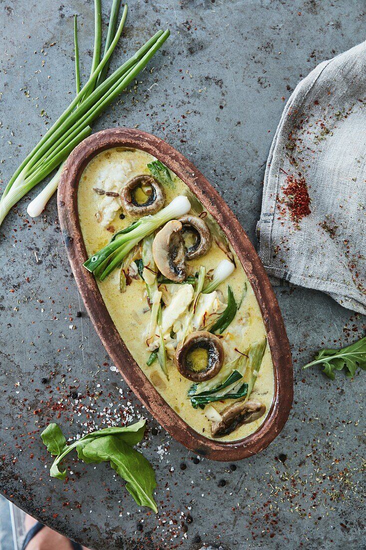 Oven cooked fish fillets with mushrooms and spring onions in cream sauce (top view)