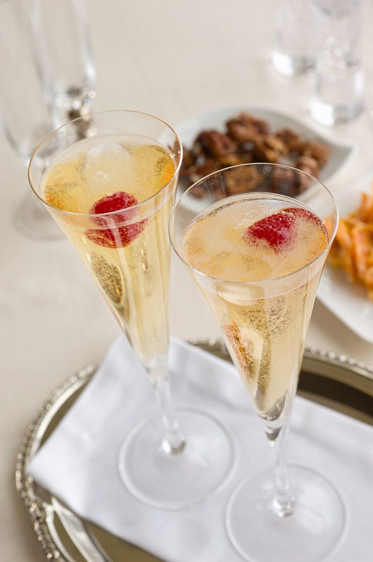 Two champagne glasses with raspberries