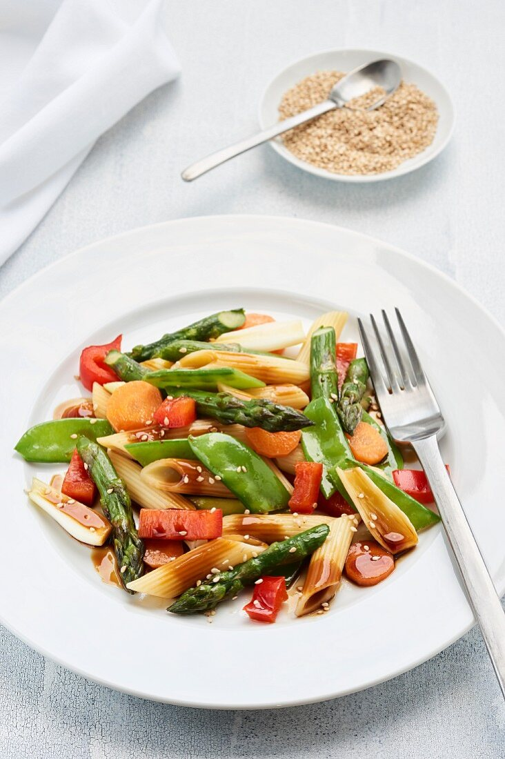 Asian style pasta salad with green asparagus, sugar snap peas, spring onions, red peppers, and carrots