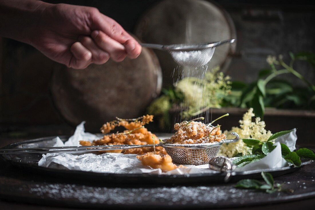 A woman's hand dusting fried elderflower blossoms with icing sugar