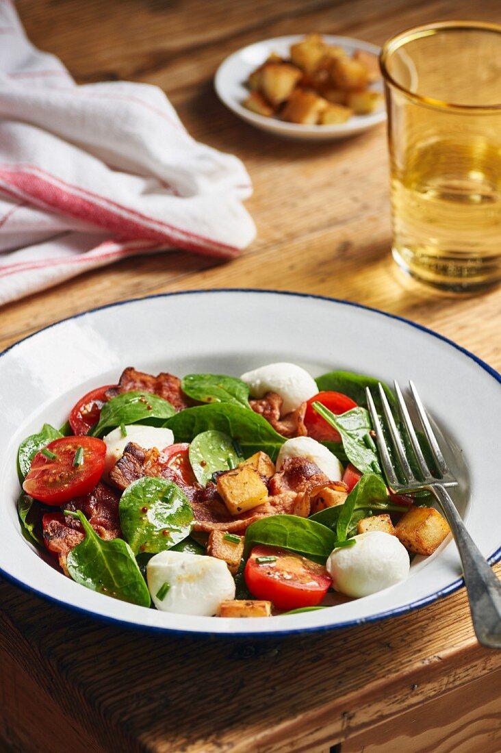 Salad with baby spinach, tomato, mozzarella, potato croutons and bacon
