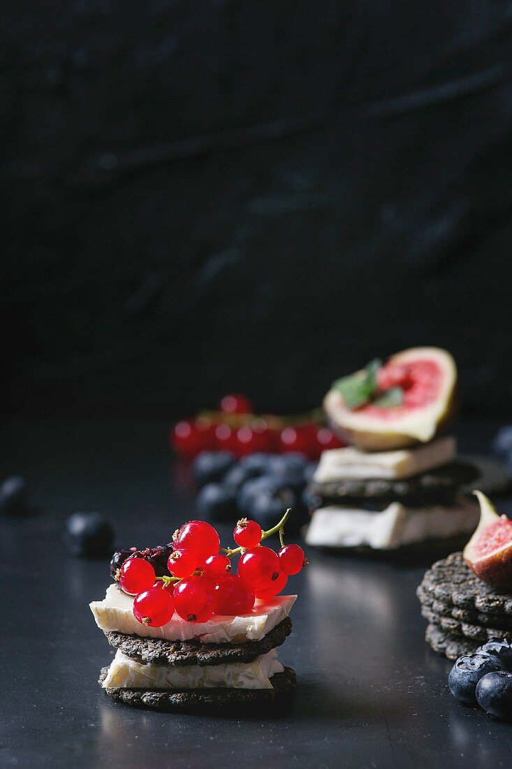 Black charcoal crackers with camembert brie cheese and berries blueberry, dewberry, red currant and sliced figs