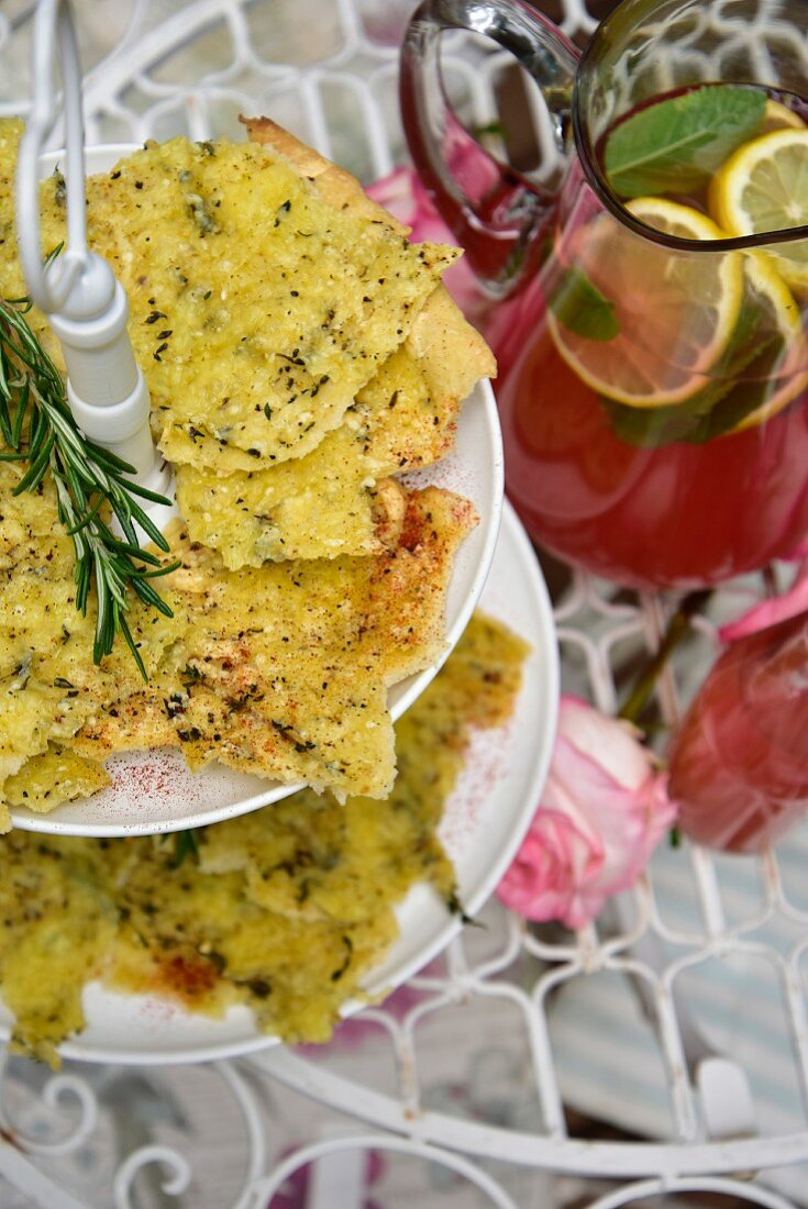 Slices of focaccia with mozzarella and herbs on a cake stand
