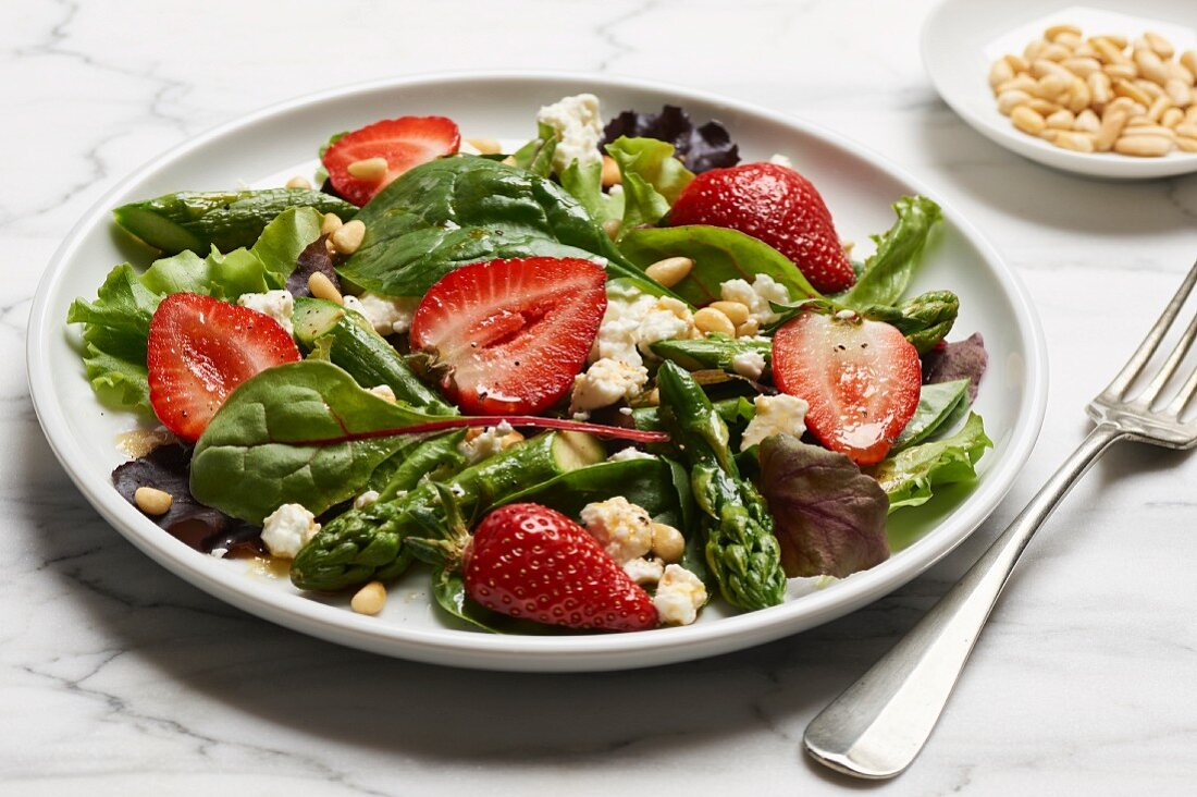Green asparagus with a mixed leaf salad, strawberries and sheep's cheese