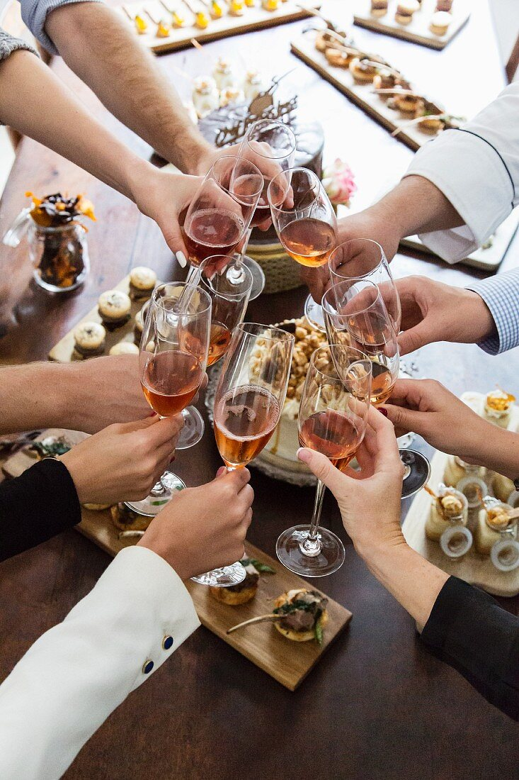 A group toasting with glasses of rose wine