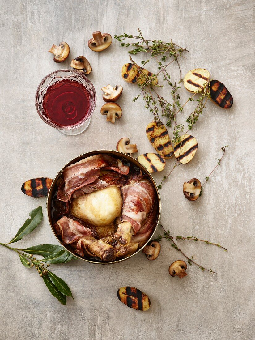 Coq au Vin with grilled potato halves, mushrooms, thyme, and a glass of red wine