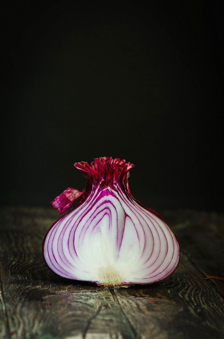 A cross section of a red onion on wooden table