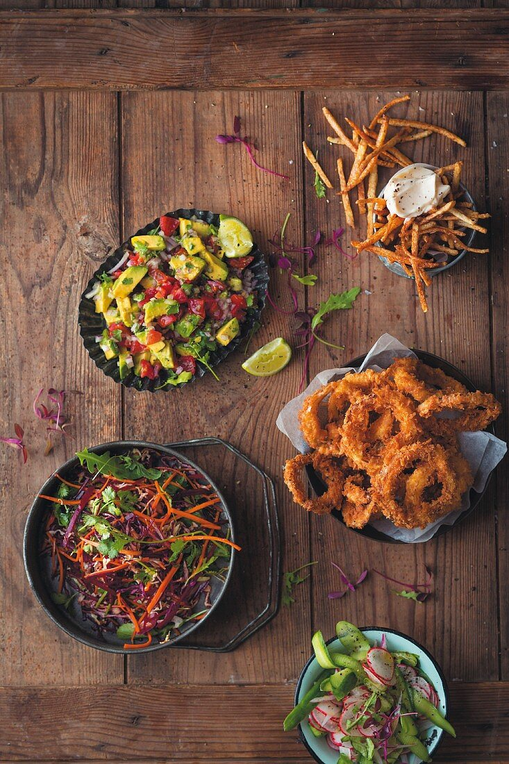 Various additional ingredients for hamburgers: avocado salsa, cabbage and beetroot salad, French fries, fried onion rings, and pickled radishes and gherkins