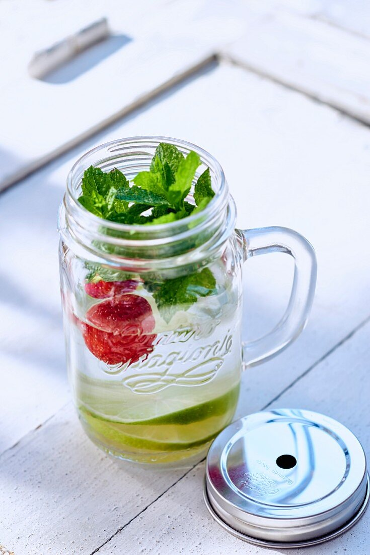 Water infused with limes, strawberries, and mint