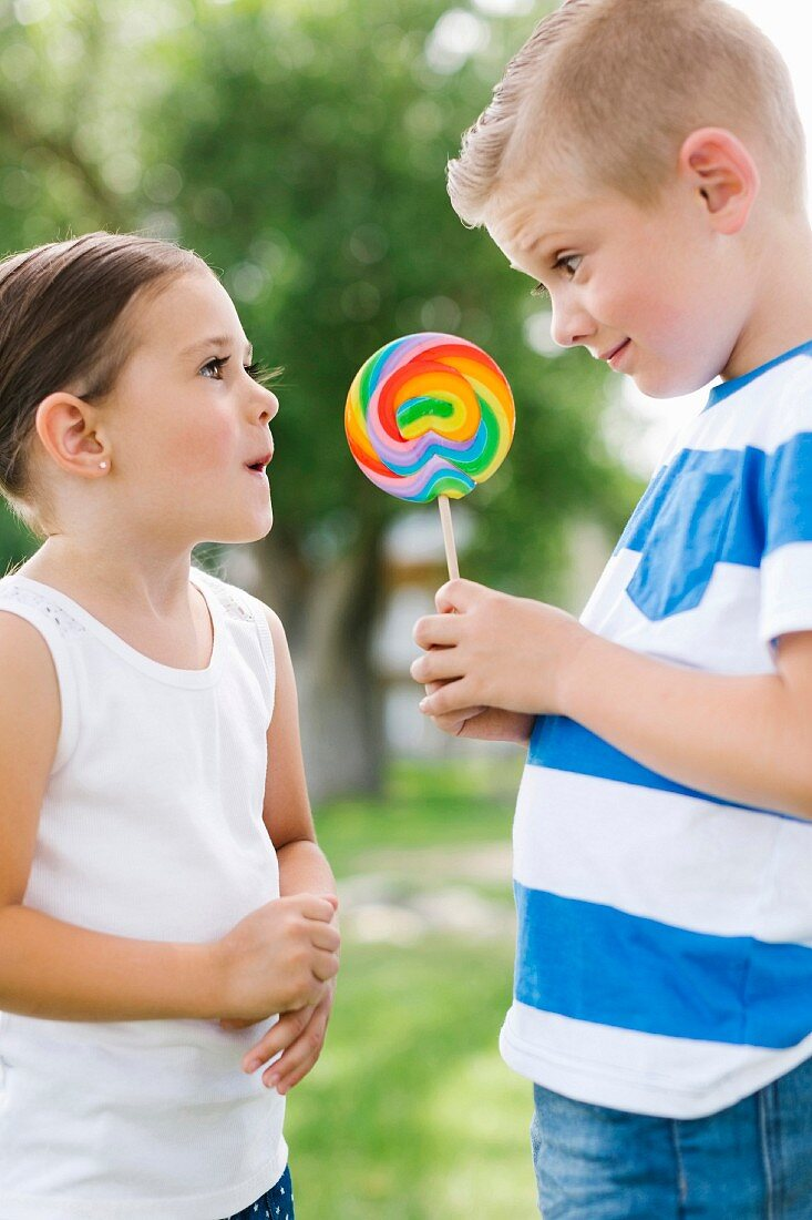 Young boy showing sister lollipop